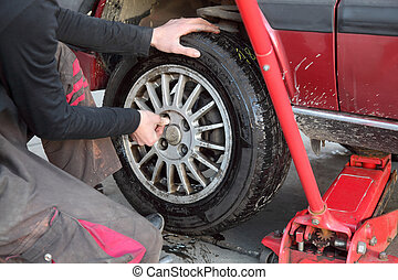 Automotive - Mechanic working on a car tire in service