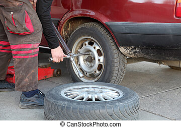 Automotive - Mechanic working on a car tire in service using...