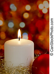 Cream candle with gold tinsel, bauble and blurred light background