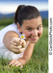 Cute smiling girl with a daisy