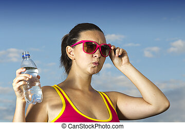 A serious cute woman with bottle