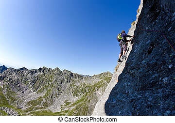 Caucasian male climber climbing a steep wall In background a...