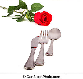 Fork, knife and spoon with a red rose in the background