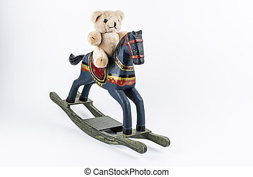 Teddybear and rocking horse - Teddybear sitting on a rocking...