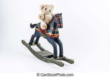 Teddybear and rocking horse - Teddybear sitting on a rocking...