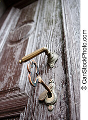 Closeup of an old wooden door with a big key in the lock