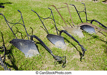 old historical metal ploughs on gras