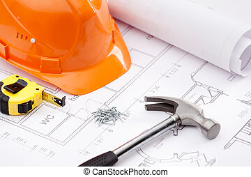 Hammer, tape measure, hard hat and nails on the draft -...