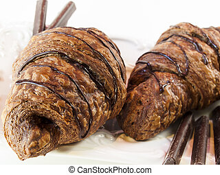 Chocolate croissant - The dough is layered with butter,...