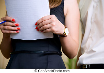 Woman holds document and man nearby in office