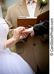 holding hands during a wedding ceremony - the bride and...
