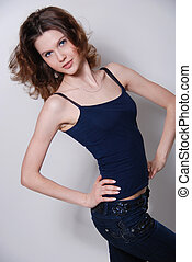 Photo of a fashion of the young harmonious woman in a fashionable vest and jeans,vertical