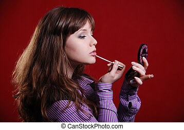 Young woman applying lip gloss a red background