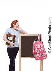 friendly Caucasian college student with backpack by blackboard
