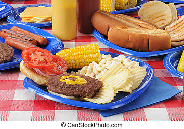A hamburger on a picnic table loaded with food - An open...