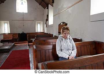 A woman sitting in an empty church praying - Mature woman...