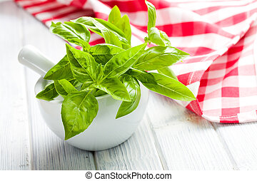 fresh basil leaves in a mortar