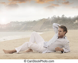 Young man - Young relaxed man laying on beach