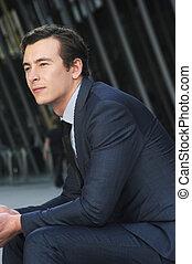 Businessman sitting on wall