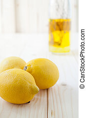 Lemons - Three yellow lemons on clear wood table