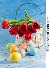 Easter eggs - Basket with red tulips, easter eggs and...
