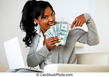 Happy young woman pointing plenty of cash money - Portrait...