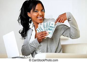 Happy woman pointing plenty of cash money - Portrait of a...