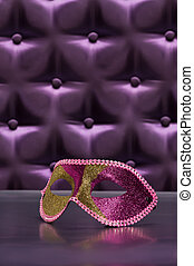 Elegant mask for Masquerade in front of a button tufted...