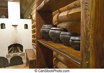 Interior of Russian log hut with the furnace and pots