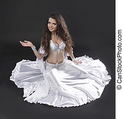 Beautiful exotic belly dancer woman over black background