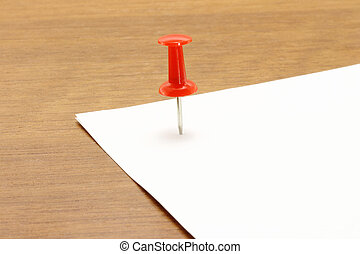 Drawing pin and piece of paper on a wooden background