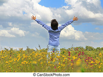 man standing on a meadow with raised hands