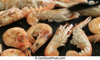 cooking - turning over grilled king prawns (on a frying pan)