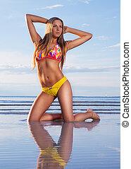 young happy woman in bikini on beach