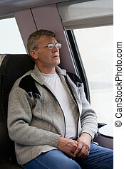 mature man wearing spectacles sits in a train car