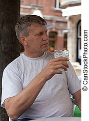 mature man keeps a glass with beer in street cafe