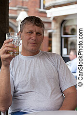 mature man holds a glass with beer and looks directly