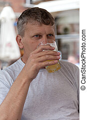 mature man drinks beer