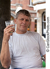 happy mature man keeps a glass with beer in street cafe
