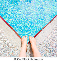 Swimming pool - A child's feet at the edge of a bright blue...