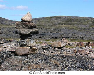 small inukshuk on tundra