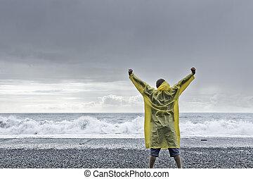 Man standing against the ocean - man in yellow rain coat...