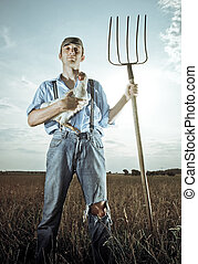 Farmer with Chicken - Young farmer standing in farm field...