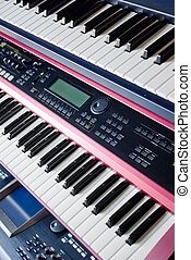 electronic music synthesizer keyboards on rack - electronic...