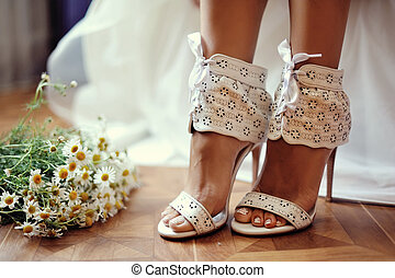 Wedding shoes - female feet in white wedding sandals with...