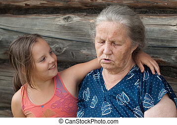 The elderly woman with the grand daughter against the wooden...