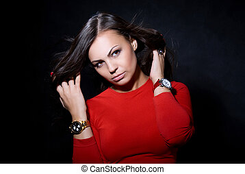 The beautiful girl with a wrist watch against a dark...