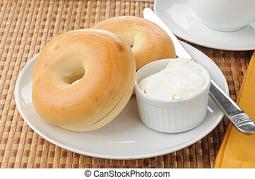 Bagels with cream cheese - A plate of sliced baglels with...