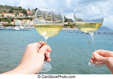 Two wineglasses in the hands against the harbour of...
