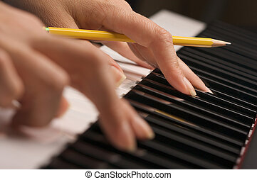 Womans Fingers on Piano - Womans Fingers with Pencil on...